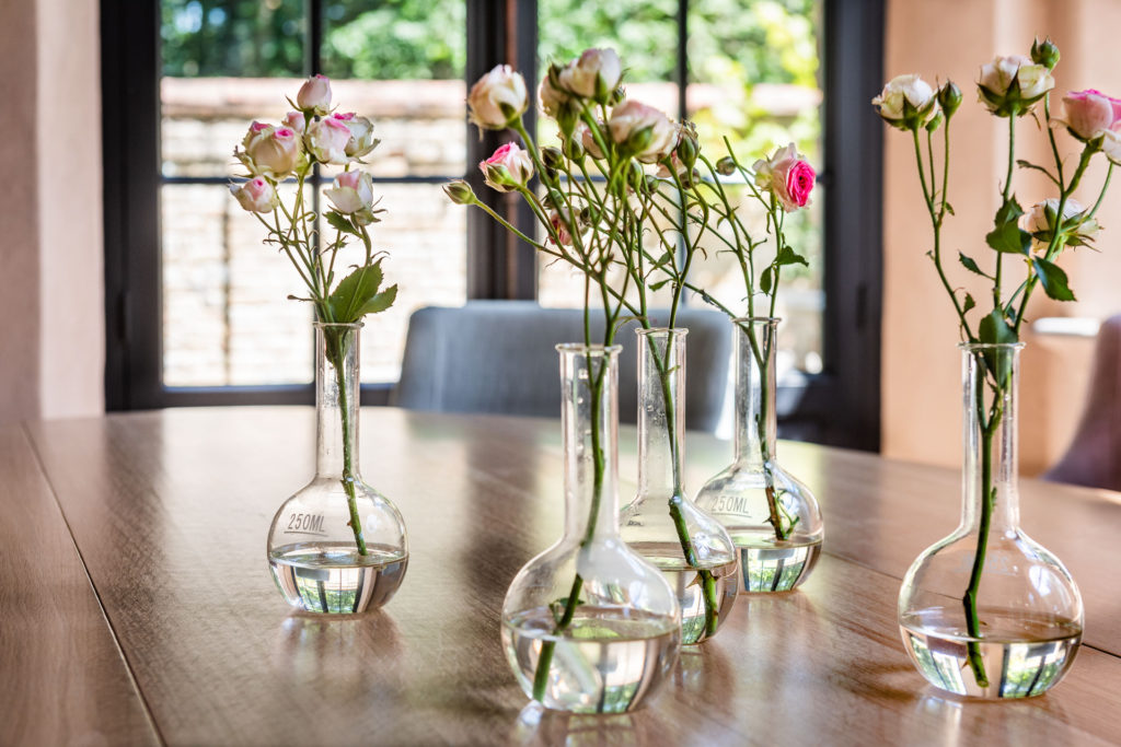 Garden roses in bud vases upon a beautiful Belgian table by Belgian Pearls Home Collection.